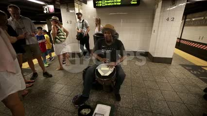 street performer musician playing conga drum in subway station interior in summer - New York City