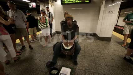 drummer playing conga drum on subway station platform in summer