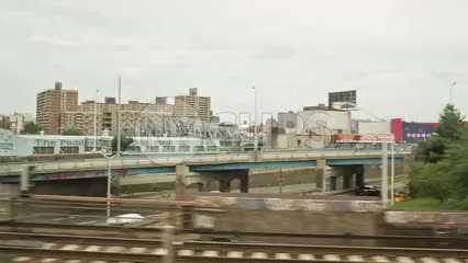 crossing Bronx River into Harlem with housing projects from moving subway train in NYC