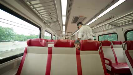 conductor punching tickets on Metro North - interior train in NYC