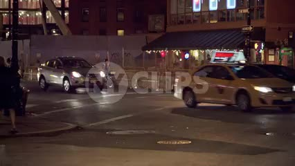 nightlife on street corner - girls walking by and cars and cabs driving in traffic on summer night in Manhattan NYC