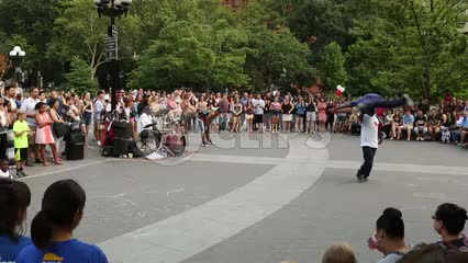 acrobats performing in Washington Square Park before a crowd - airplane spin on head on summer day in NYC