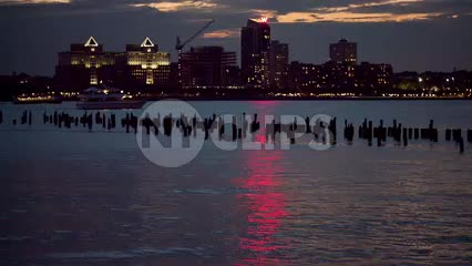 New Jersey skyline buildings and the W Hotel across Hudson River at night with wood dowels in water from Manhattan NYC