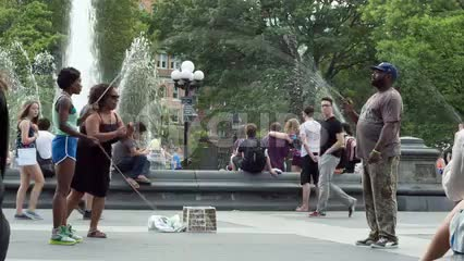 woman with double-dutch skills in Washington Square Park on summer day with sprinkler in background in NYC