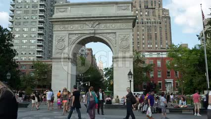 people walking past Washington Square Park arch on summer day in late afternoon in New York City