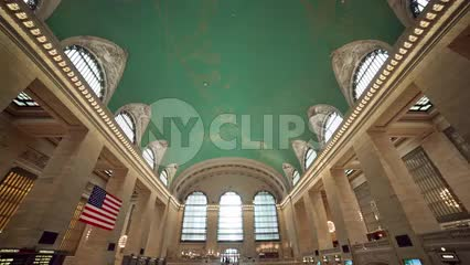 tilting down from Grand Central Station ceiling to stairs below with people in crowded room in summer NYC