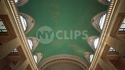 tilting down from Grand Central Station terminal ceiling to information desk with clock and people waiting in NYC