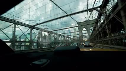 driving across Brooklyn Bridge - view of Manhattan skyline in rear window view in NYC