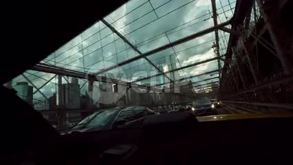 view out backseat - rear windshield of taxi cab driving across Brooklyn Bridge on cloudy day in NYC