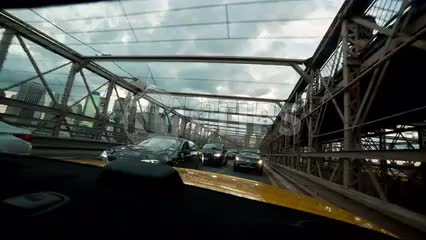 taxi interior rear windshield crossing Brooklyn Bridge on cloudy day in NYC