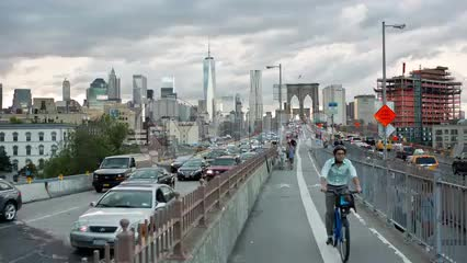 cars and bicycles exiting Brooklyn Bridge with view of Manhattan skyline in distance in summer late afternoon in NYC