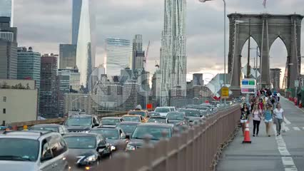 Freedom Tower view from Brooklyn Bridge with tourists walking across and cars driving in traffic on summer day in NYC