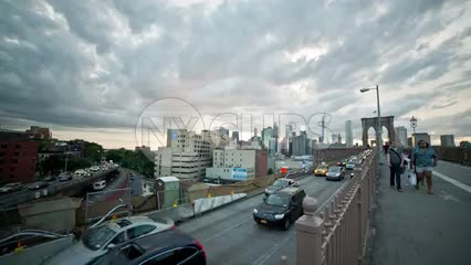cars in traffic entering Brooklyn off bridge on summer evening - beautiful sunset clouds in NYC