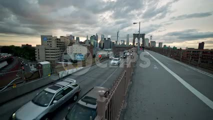 cars driving on Brooklyn Bridge from Manhattan, pedestrian path at sunset, summer evening in NYC