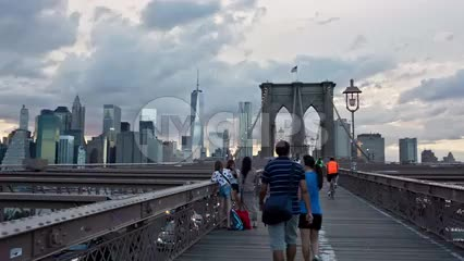 panning across Brooklyn Bridge pedestrian path - people walking in early evening summer day around sunset in NYC