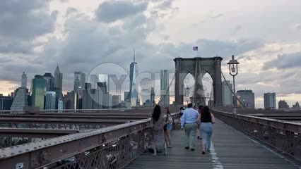 Brooklyn Bridge with Freedom Tower and Manhattan skyline at sunset with clouds in sky