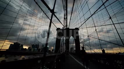 Brooklyn Bridge at sunset in early evening with people crossing - silhouette in NYC