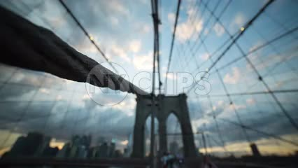 close-up of suspension rope on Brooklyn Bridge with sunset and tourists out of focus in NYC