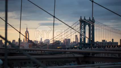 Manhattan Bridge and Empire State Building view from Brooklyn Bridge at beautiful sunset in early evening in NYC