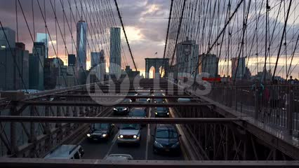 cars driving in slow traffic across Brooklyn Bridge at sunset with Manhattan skyline in background in NYC