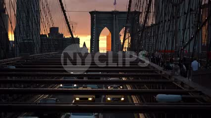 Brooklyn Bridge interior view over cars driving slowly in traffic below at sunset in NYC