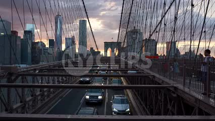 cars driving slowly in traffic over Brooklyn Bridge at sunset with Manhattan skyline in background - Freedom Tower and skyscrapers in New York City