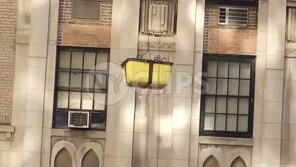 bucket lowering down side of building to construction workers at site in hardhats in NYC