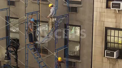 construction workers on building scaffolding in hardhats in NYC