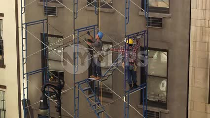 construction workers in hardhats on scaffolding - man doing pull-ups on his break in NYC