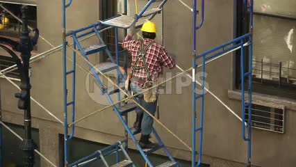 construction worker in hardhat climbing scaffolding on building in NYC