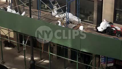 scaffolding on side of building with construction workers in yellow hardhats climbing and working in NYC