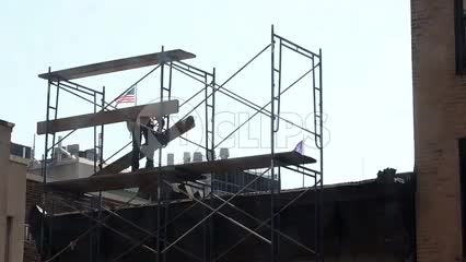 construction worker laying wood plank on scaffolding at top of building, man in hardhat on rooftop with American flag