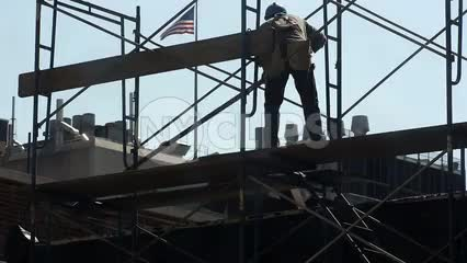 construction worker laying down wood plank on scaffolding - man in hardhat with American flag on roof in NYC