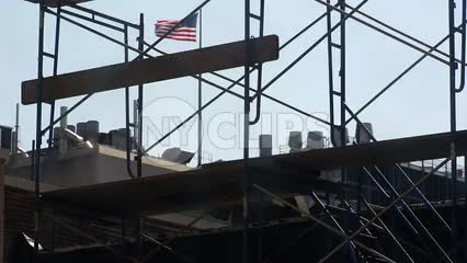 construction scaffolding with American flag on building rooftop waving in background in NYC