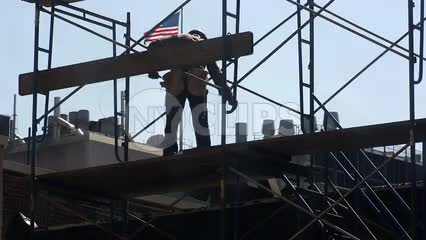 construction worker on scaffolding - man in hardhat with American flag in background in New York City