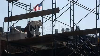construction worker in hardhat hammering scaffolding on rooftop of building with American flag waving in NYC