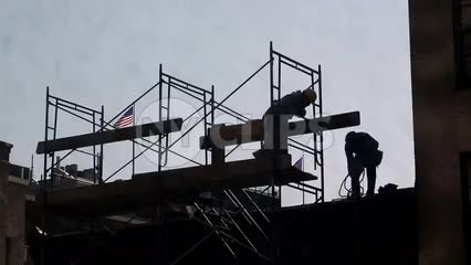 silhouette of construction workers in hardhats on scaffolding at top of building with American flag waving in NYC