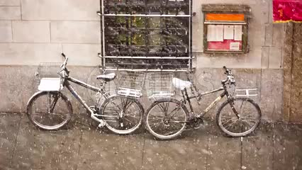 two bicycles outside in snow storm on street in NYC