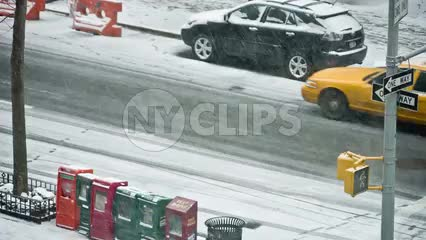 taxicab driving in snow - snowing in NYC - winter blizzard with newspaper vending machines