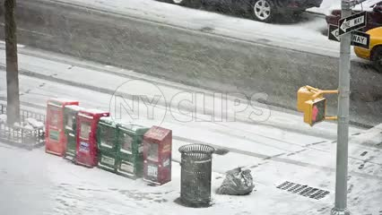 newspaper dispensers and garbage can on corner in snow storm - snowing winter blizzard