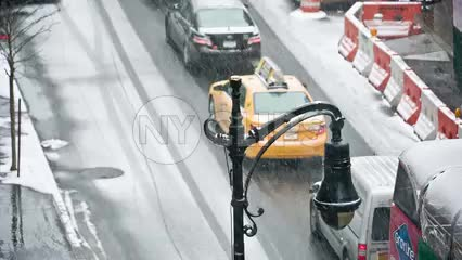 blizzard in Manhattan overhead shot double decker tour bus driving in snow snowing on street winter NYC