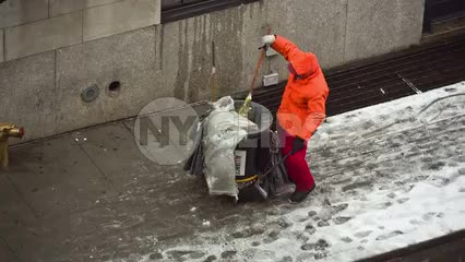 street cleaner man in orange coat on cold winter day with snow on ground in NYC