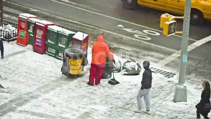 sanitation man in orange jacket shoveling snow on corner in blizzard on winter day snowing in Manhattan NYC