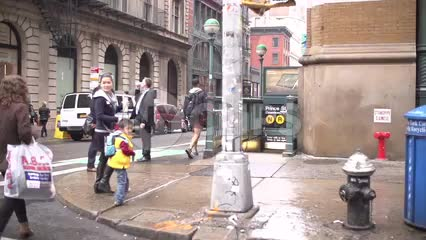 super slow motion of people walking on Broadway and Prince street by subway entrances in SoHo NYC on wet fall day
