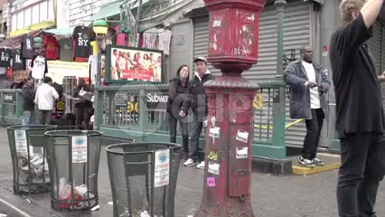 Asian man leaning on Canal Street Chinatown subway entrance giving middle finger in slow motion NYC