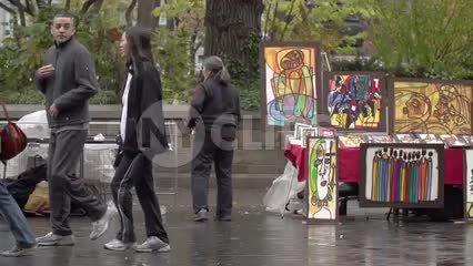 art on display at Union Square Park on street on wet fall day in NYC