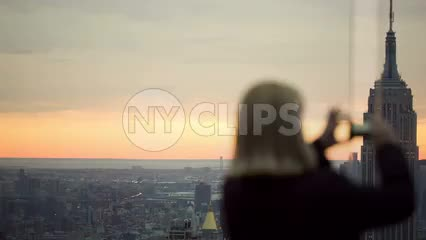 tourist woman taking picture of Empire State Building from high view at sunset in 1080 HD in NYC