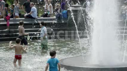 kids playing in water sprinkler - fountain in Washington Square Park on summer day in NYC