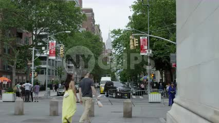 couple walking under Washington Square Park arch on summer day in NYC