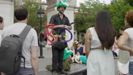 street performer making balloons for people in Washington Square Park on summer day in NYC